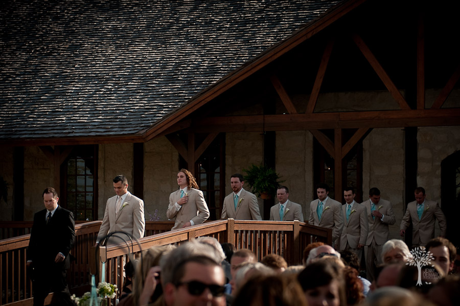 Groom and the groomsmen walk out to the ceremony in a single line. The groomsmen are wearing tan suites with Tiffany blue ties. bridge, outdoor ceremony