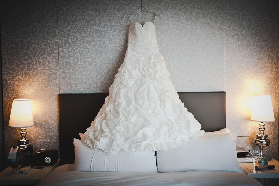 The bride hangs her gorgeous ruffled wedding dress against the wall of the four seasons while getting ready for her wedding ceremony.