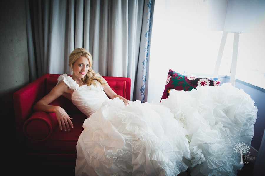 Caroline poses on The W Hotel's stylish red couch during her bridal shoot in Austin.