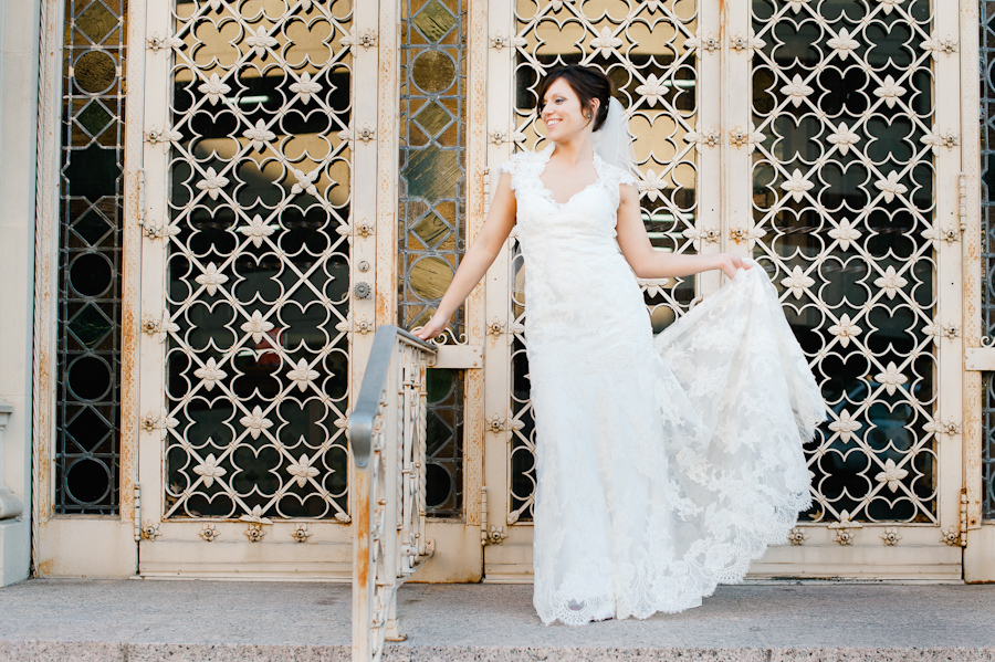lace bridal gown with collar infront of iron gates at Central Christian Church in Austin, Texas