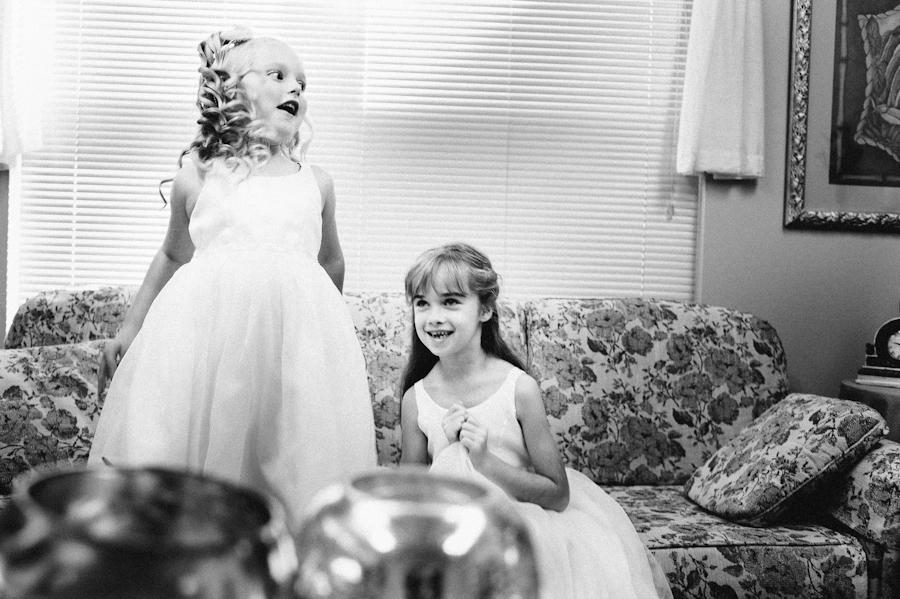 flower girls excited before the wedding jumping on the couch