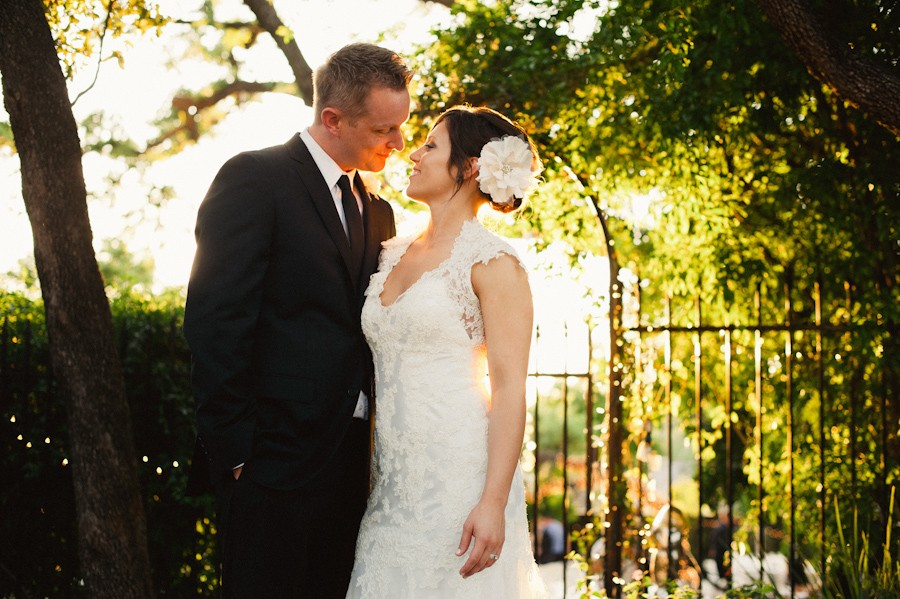 Bride and groom kiss in the sunset at their wedding reception at The Allan House in Austin, Texas.