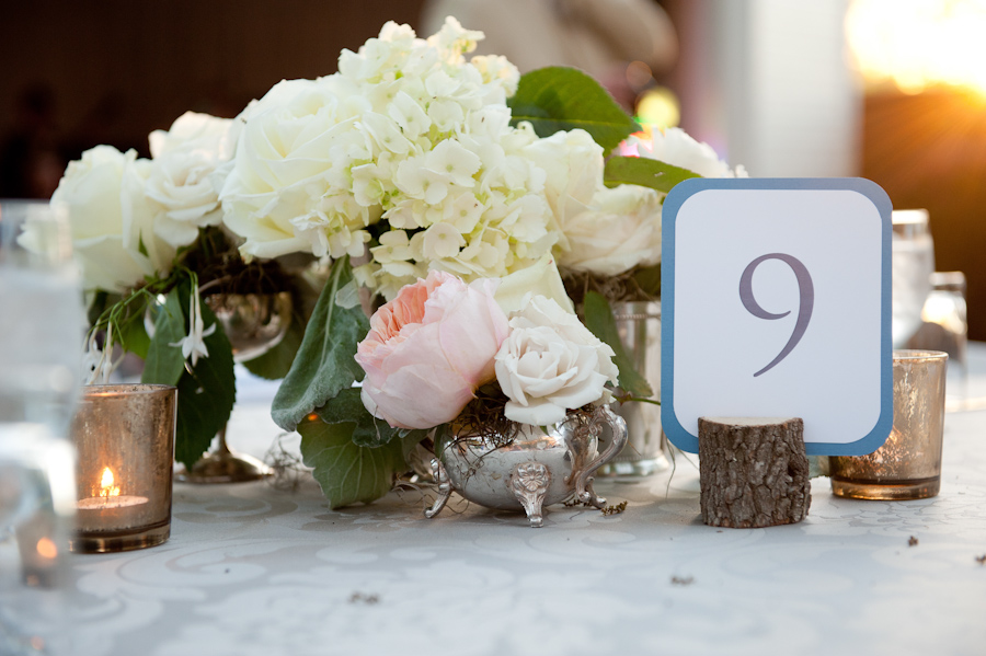 table centerpices, wooden tree branch circles to hold table number signage, pastel florals in antique silver vases