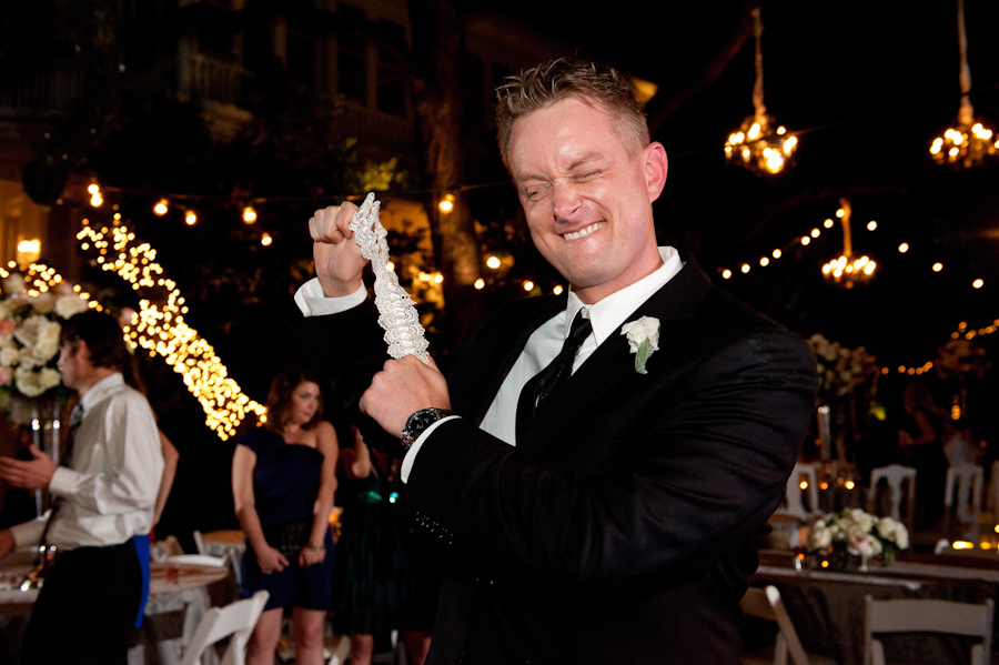 groom slingshot the garter at an evening outdoor wedding near downtown Austin