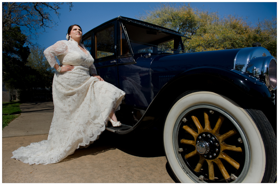 bride in front of antique car with wooden spokes Allure Couture gown and Antonio Melani shoes