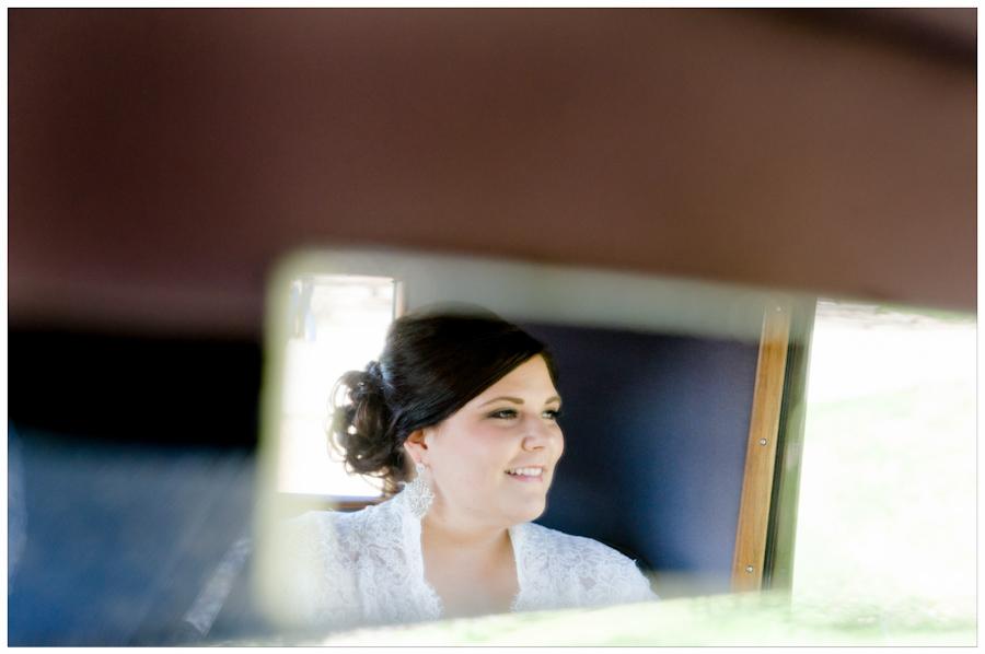 Bride in rear view mirror on antique car