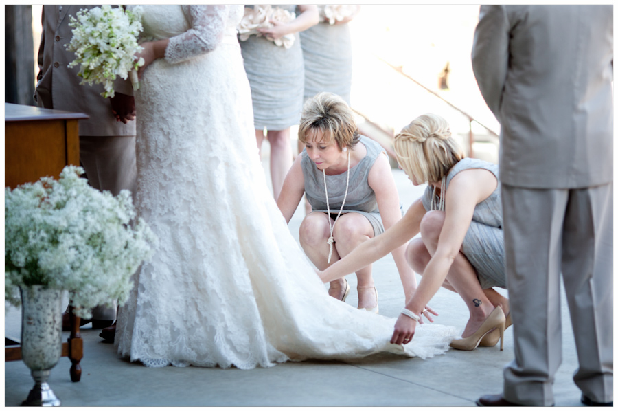 bridesmaids fixing bridal gown during ceremony Allure Couture lace gown