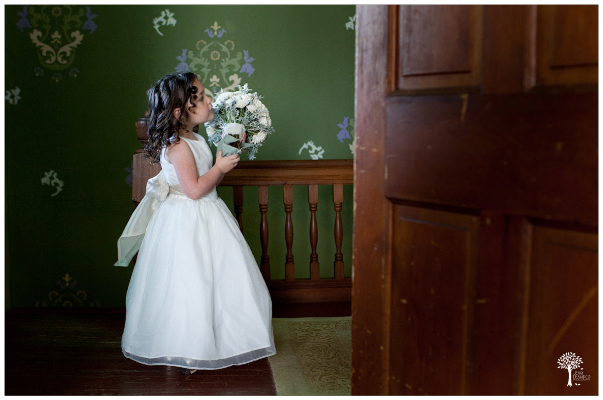 flower girl holding brides bouquet at the barr mansion in sprinke texas