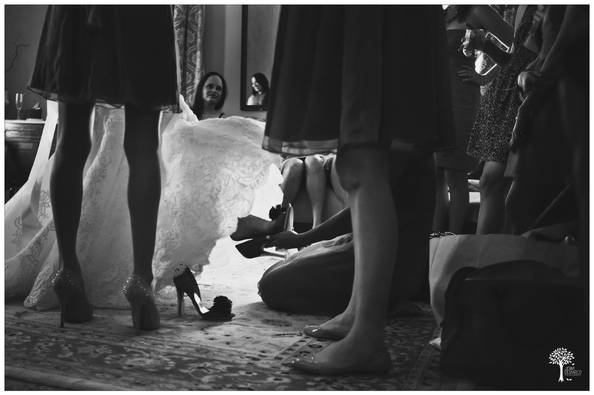 Bride putting her Badgley Mischka shoes with help of bridesmaids