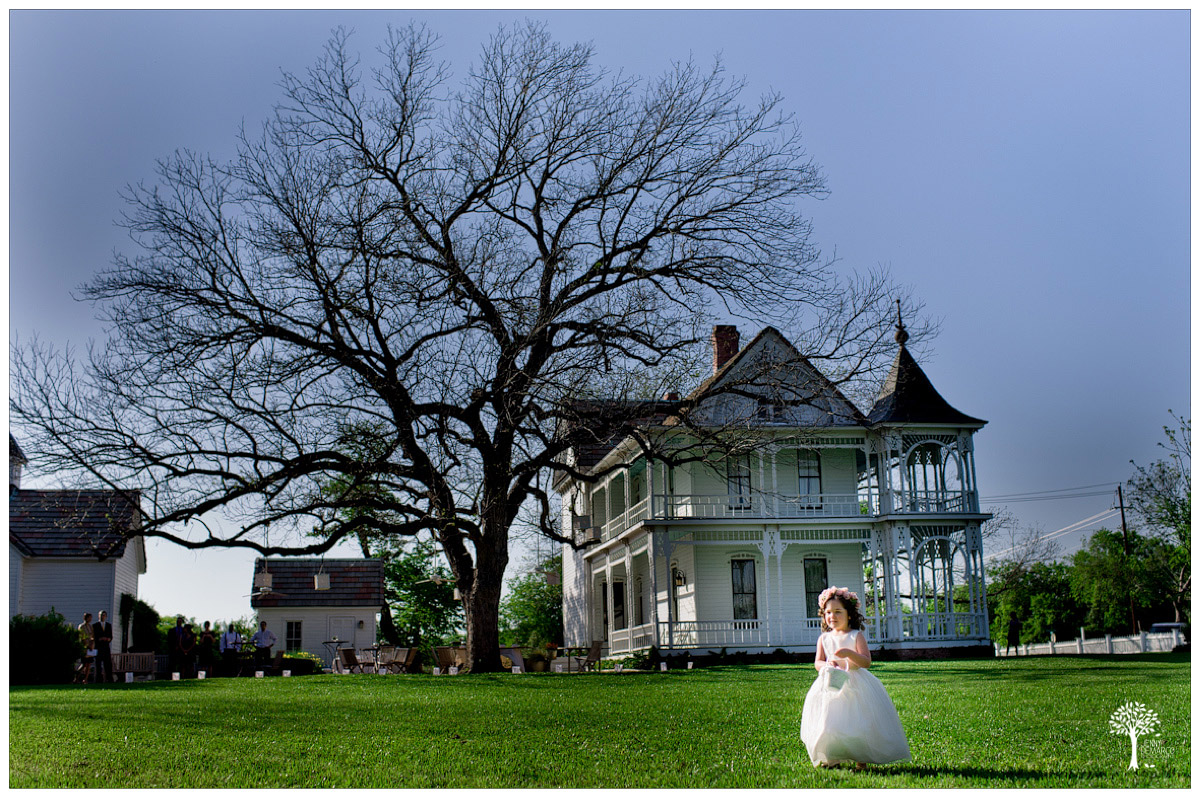 Flower girl walking across lawn at Barr Mansion to ceremony site
