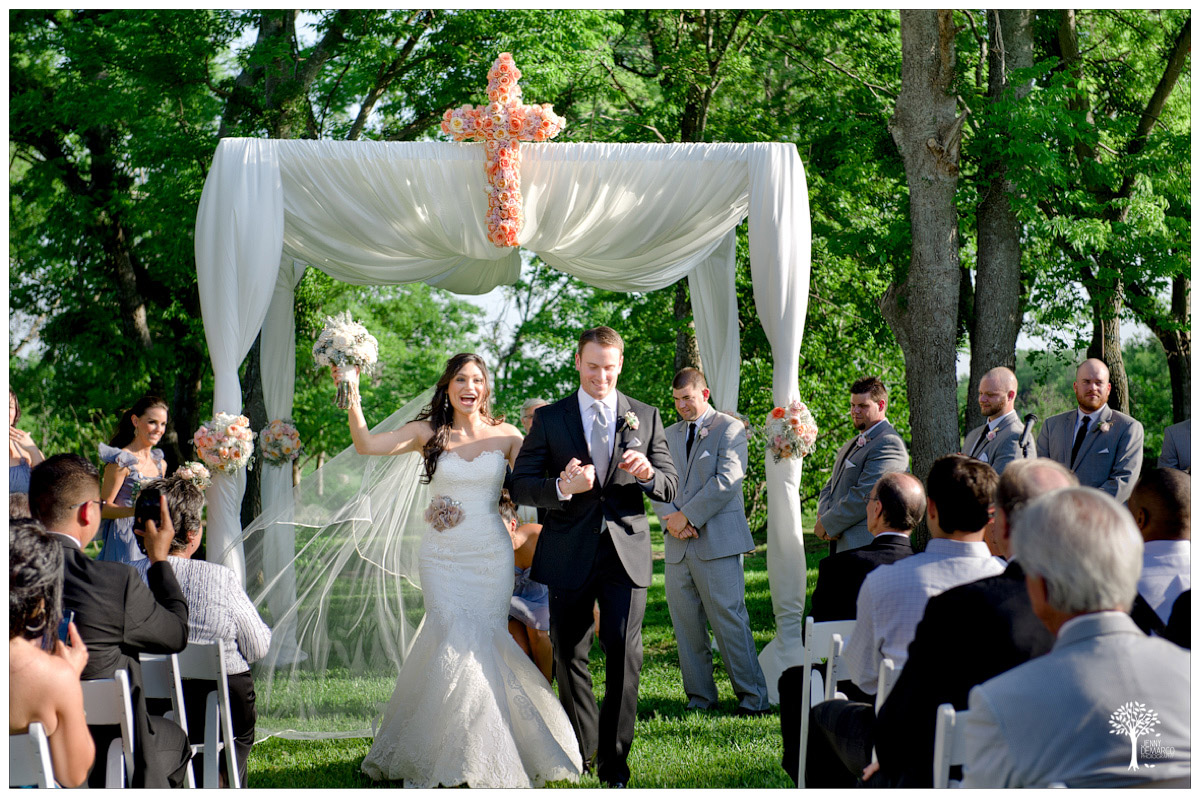 bride and groom ceremony recessional with large floral cross in the background