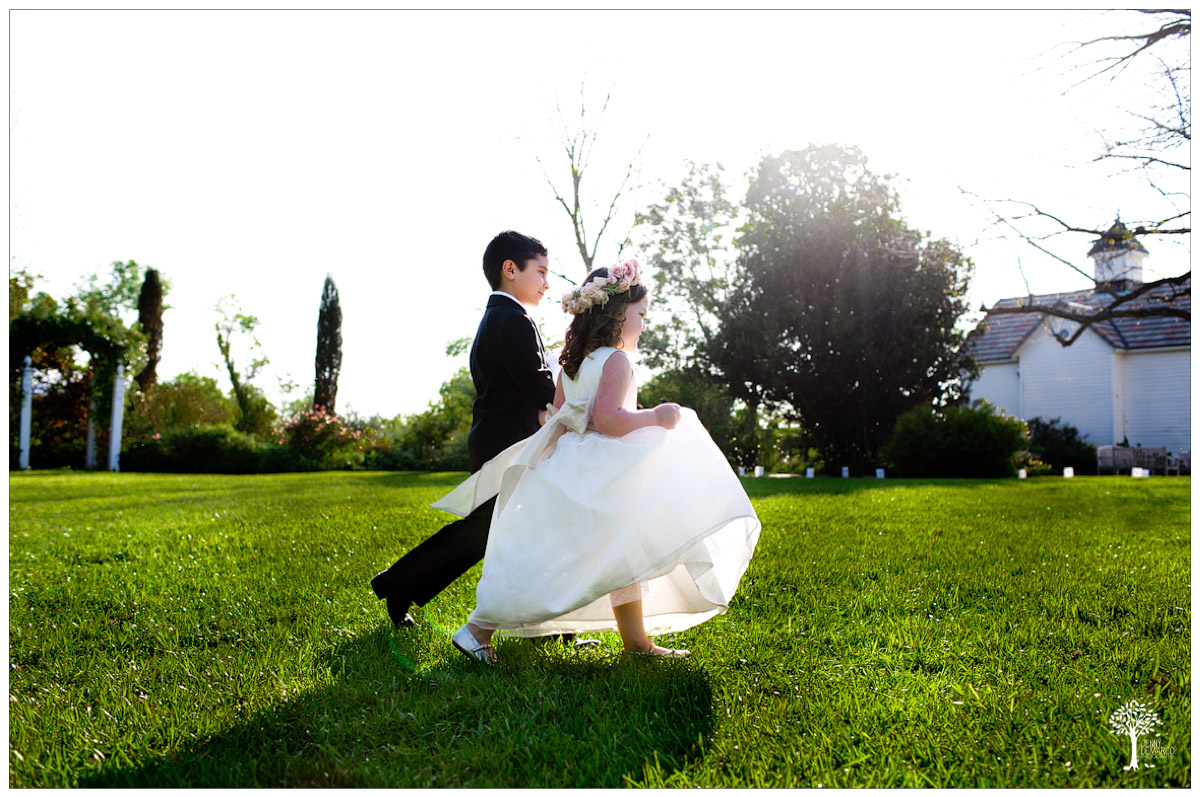 cute flower girl and ringbearer exiting cremony across the lawn