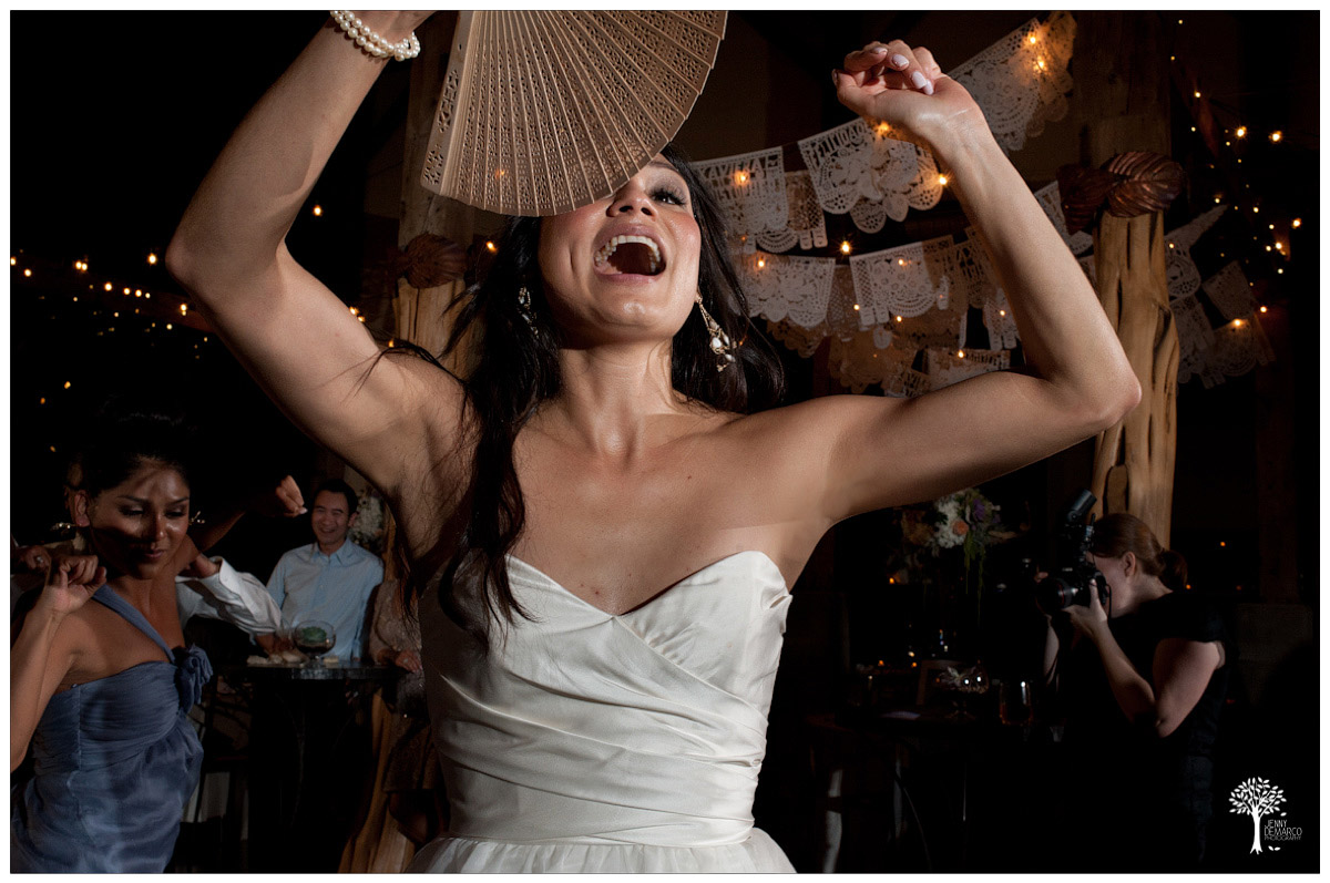 bride dancing with wooden fan from the ceremony