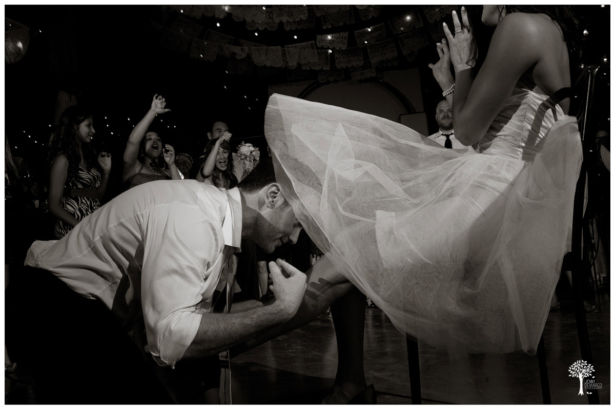 groom taking off brides garter