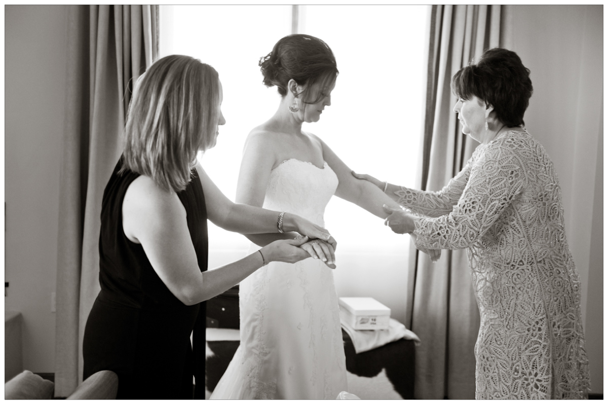 bridesmaids and mother of the bride helping bride get dressed