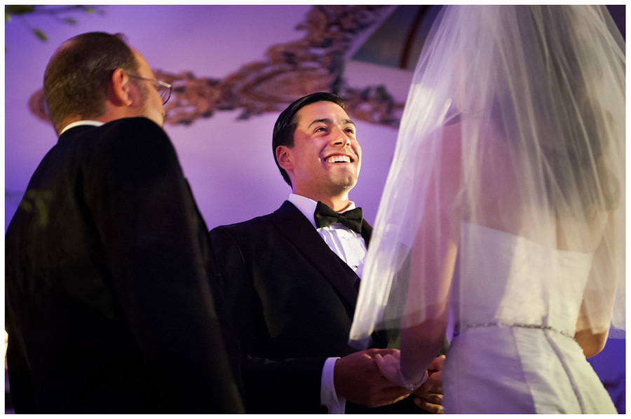 handsome groom in black tux smiling at bride