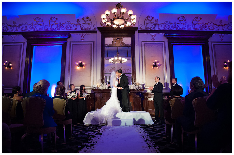 kiss and dramatic lighting in the driskill ballroom near the mantal