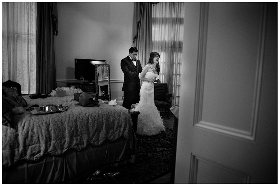 groom fixing brides dress in the heritage suite