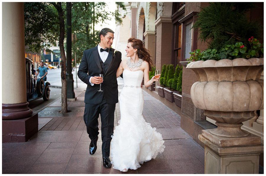 bride and groom walking downtown congress avanue wiht champaign glasses
