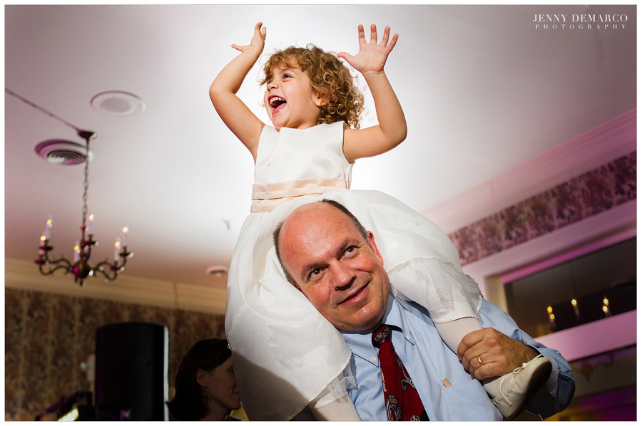 cute flower girl dancing on daddy's shoulders