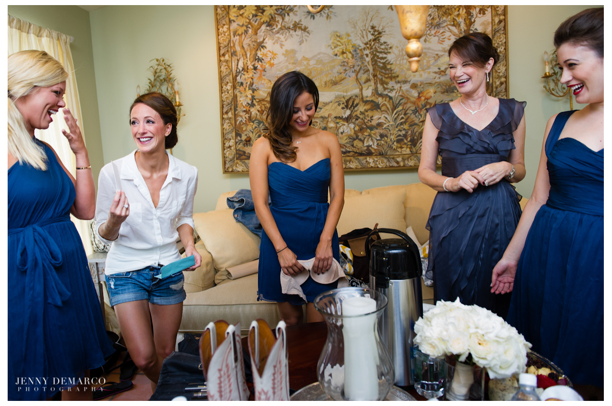 The bride laughing with her bridesmaids while they get ready.