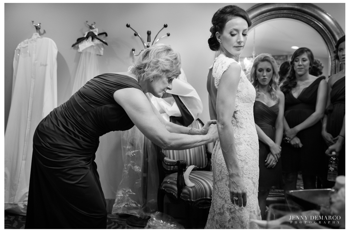 The mother of the bride helping the bride into her Monique Lhuillier dress.
