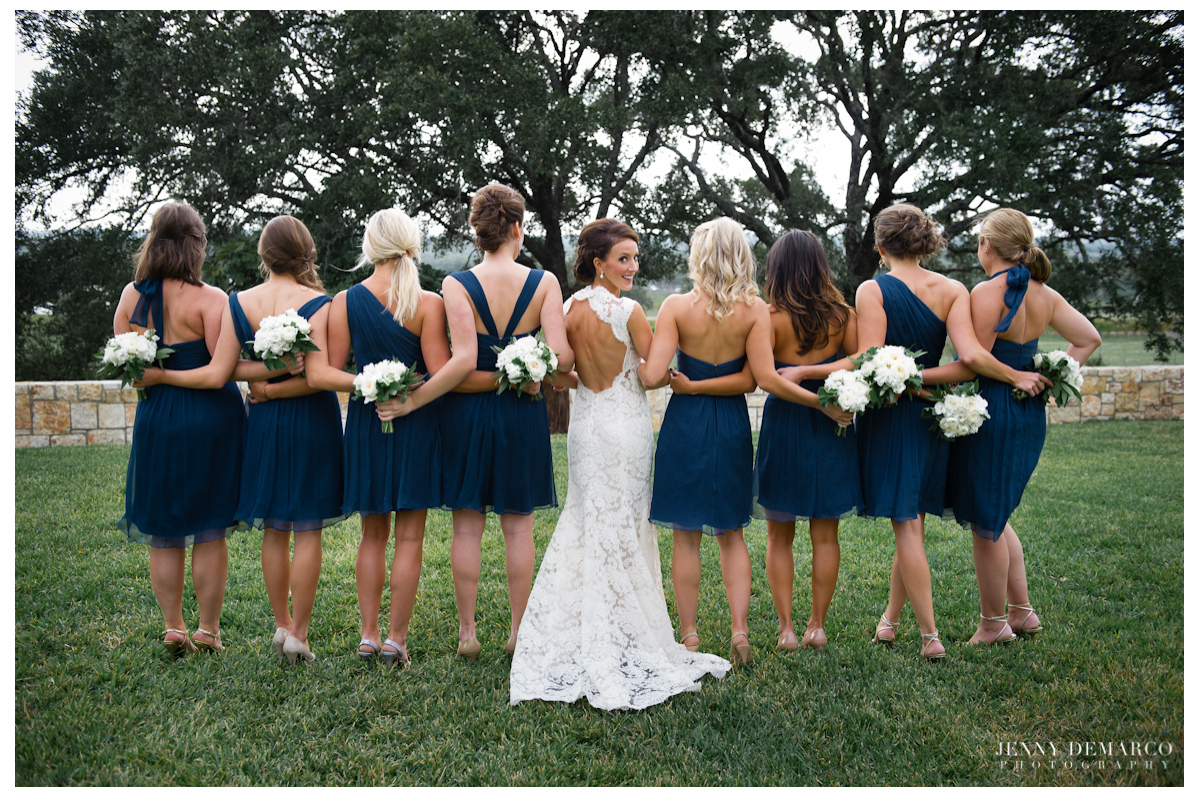 The bride and her bridesmaids showing off the different style backs of their Amsale bridesmaid dresses.