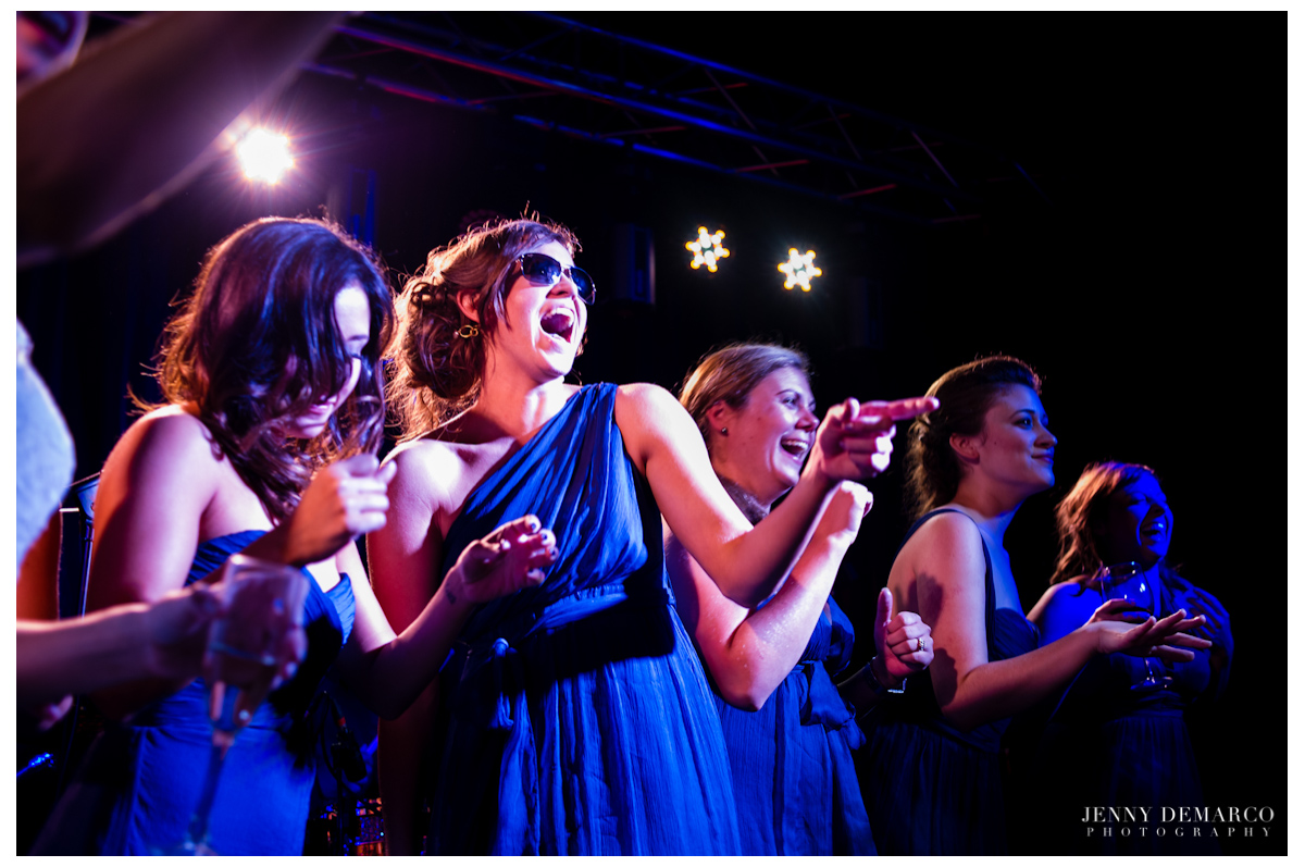 The bridesmaids on stage singng the night away at the reception.