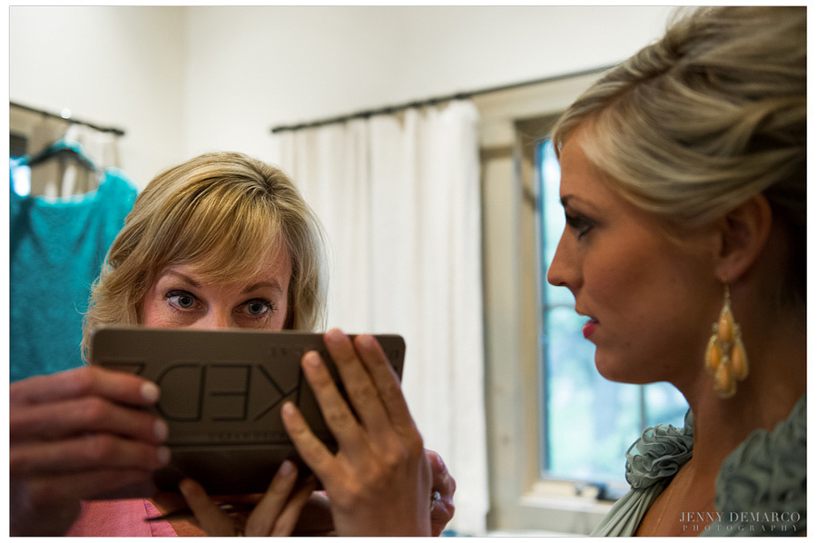 Bride and mother check out the reflection in the Naked Palette by Urban Decay makeup for the wedding.