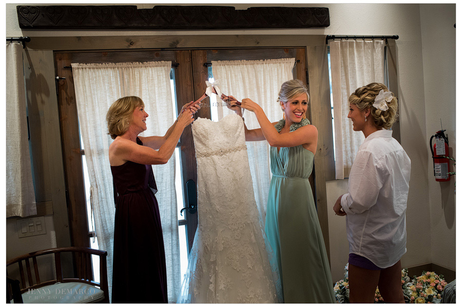Maid of Honor and Mother of the Bride help get down the brides wedding gown that was hanging in the adorable bride's cottage.