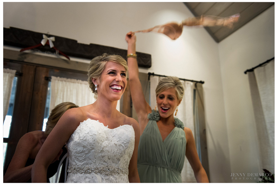 Bride puts on her high-fashion wedding dress and laughs at bridesmaid's antics.