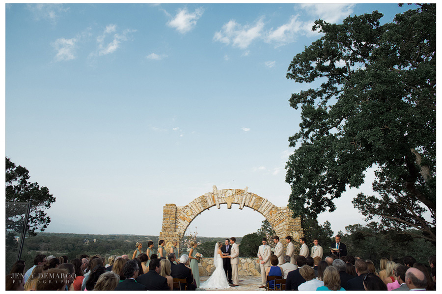 Wedding ceremony takes place under the stone arch while guests are seated on the outdoor patio.