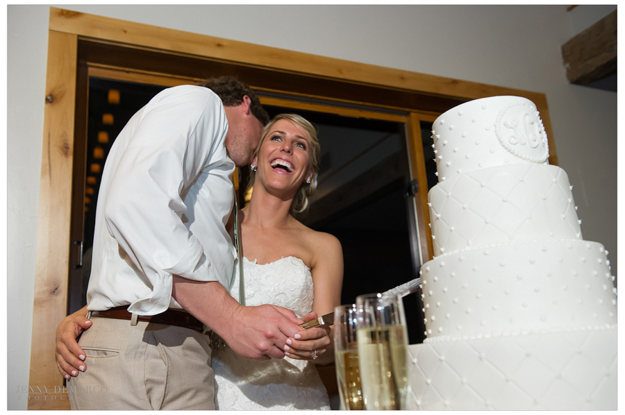 Bride and groom before their wonderfully detailed, beautiful white wedding cake.