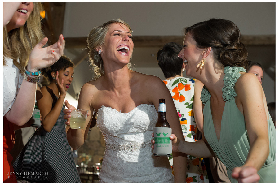 Joyful bride and bridesmaids laugh at Sacred Oaks wedding.