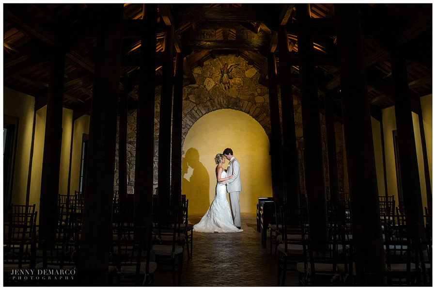Bride and groom embrace in the French Colonial Chapel at Camp Lucy in the beautiful Texas Hill Country.