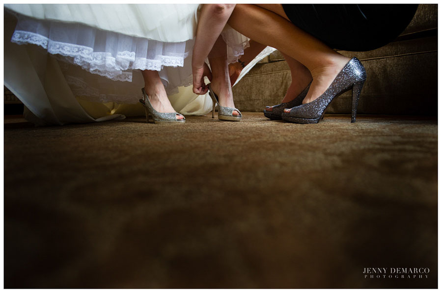Bridesmaid putting on bride's Jimmy Choo shoes in downtown Austin.
