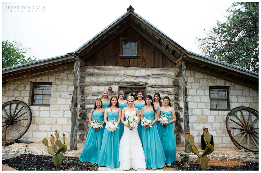 The bride and bridesmaids pose for a picture by one of Austin's top wedding photographers in a ranch wedding.
