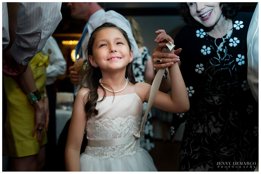 A happy flower girl watches the dance floor at the wedding reception.