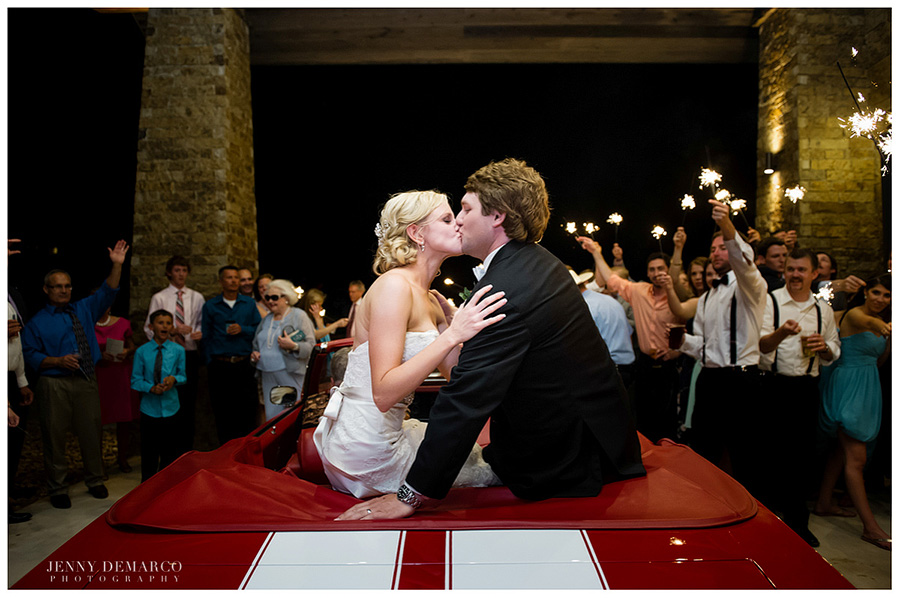 The bride and groom kiss at their Hill Country ranch wedding on top of a flashy red sports car.