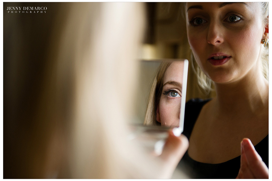 The beautiful bride getting her makeup done by the makeup artist as she looks at her relection in the mirror.