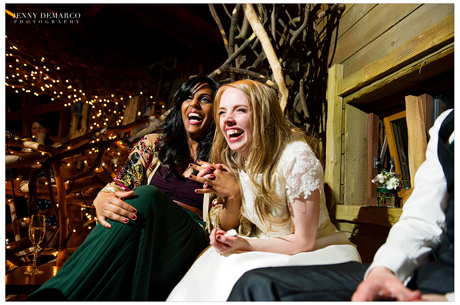 The bridesmaid and bride laughing over the toasts.
