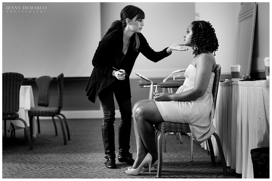 A wedding makeup artist carefully does up the bride's elegant makeup.