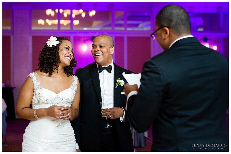 The happy couple laugh at a groomsman's speech in the ballroom reception.