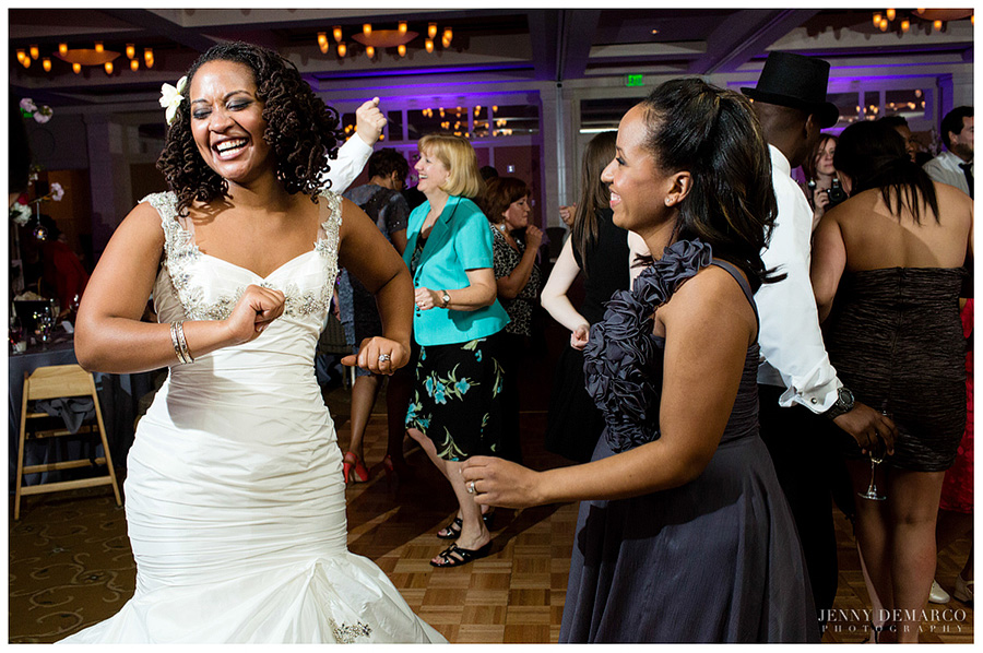 The bride dances at the posh wedding reception with a friend.