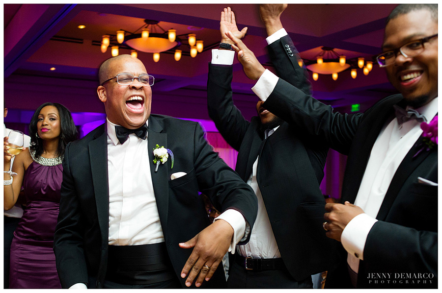 A happy groom laughs with the groomsmen on the ballroom dance floor.
