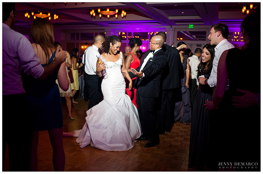 Towards the end of their fashionable wedding reception, the bride and groom dance in the ballroom.