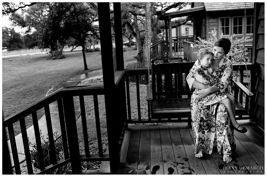 The bride and her daughter, the flower girl, take a moment on the rustic front porch of the Storybook Bride's Cottage.