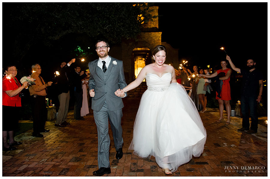 The joyous bride and groom walk away from the French Colonial Chapel at the end of their fun-filled wedding reception at Camp Lucy in the Texas Hill Country.