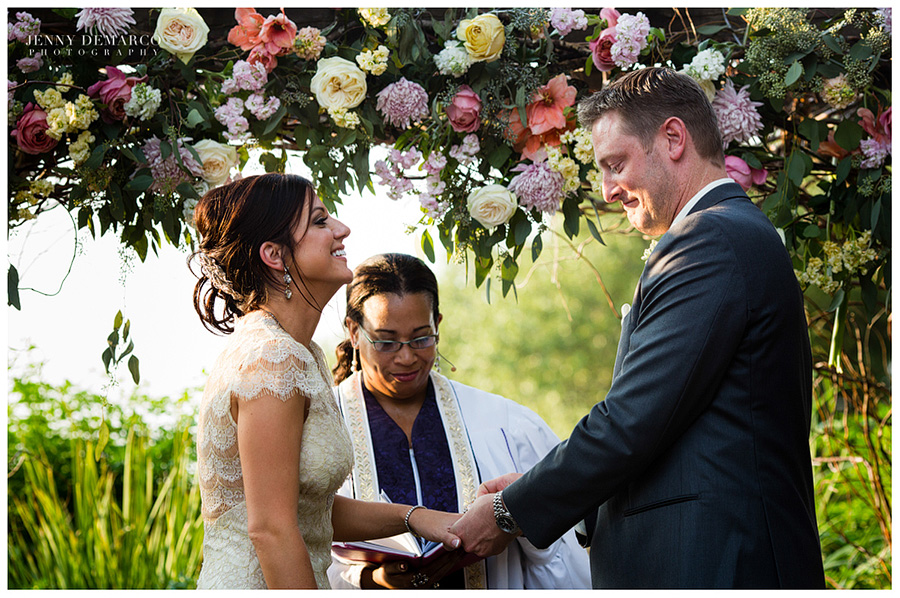 The lovely ceremony featured an arch filled with vibrant flowers.