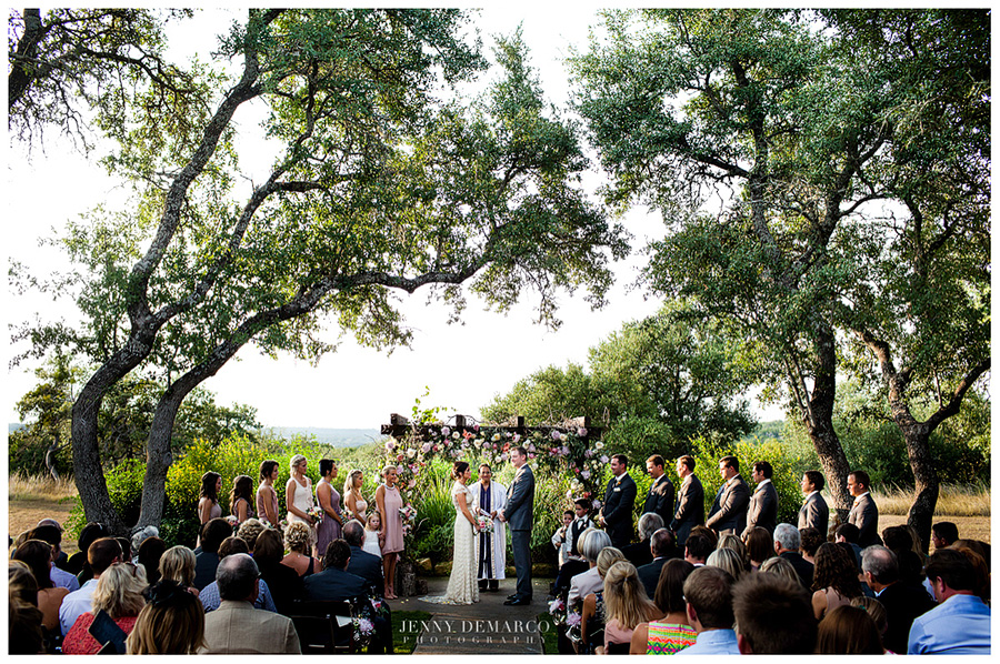 The bride and groom take hands at Vista West Ranch's gorgeous floral alter during their wedding ceremony.